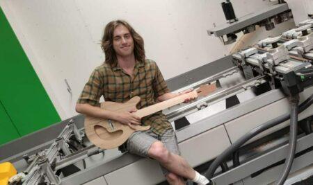 Tom maakt gitaar op stage